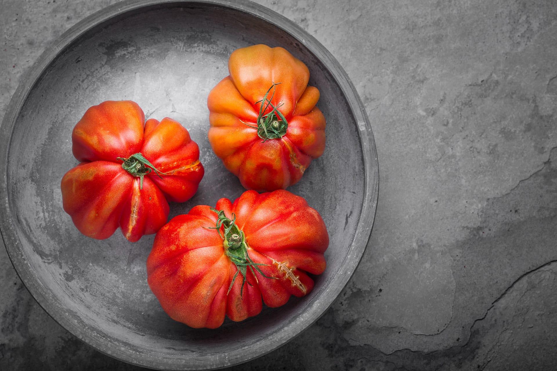 pomodori rossi cuore di bue su piatto in cemento e fondo di pietra fotografia food editoriale advertising ristorazione udine treviso gorizia friuli venezia giulia veneto nord italia